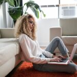 Woman sits on the floor with her laptop while working remotely from home